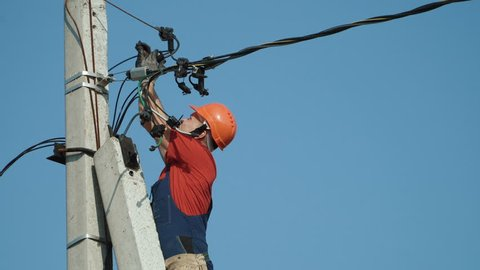 An electrician working at a newly installed utility pole - connects a new power line.