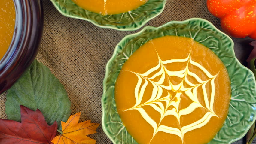 Serving hot pumpkin soup into green leaf bowls and making spiderweb cream decorations, on a rustic background for Happy Halloween party food, close up pan and zoom out.