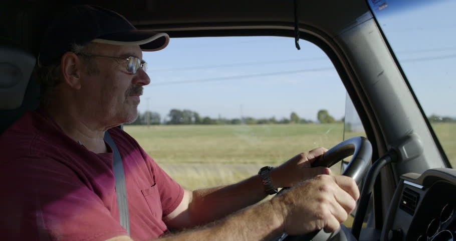 Profile view of man wearing burgundy T-shirt, glasses and cap, driving truck past farmland on a warm summer day. Interior, hand-held slow motion 4K recorded at 60fps.