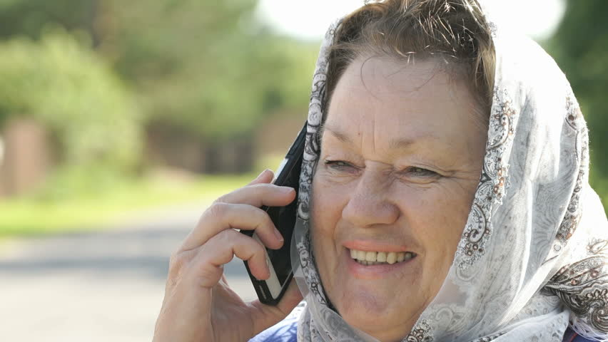 Smiling adult woman dressed in a handkerchief on the background of road in the village in summer stands and talks to relatives using a silver mobile phone. Close-up