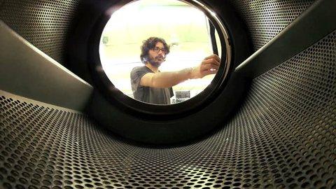 Man does laundry - Shot from inside washing machine