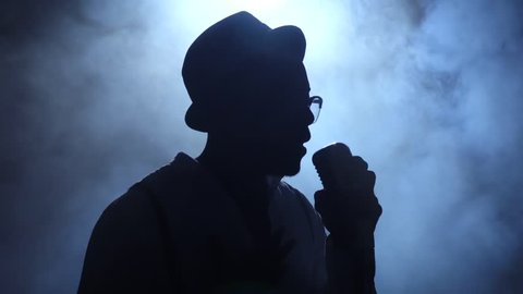 African American man comes out of the smoke to the microphone singing in a dark recording studio. Black background. Silhouette. Slow motion. Close up