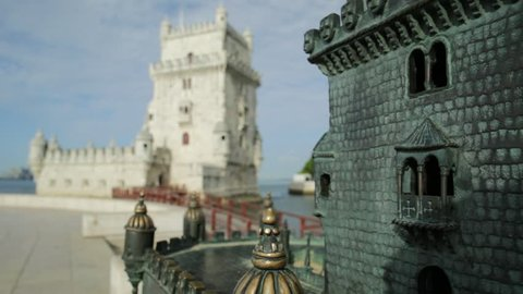 small Belem Tower bronze statue in front of real Belem Tower of Lisbon, in Belem District on Tagus River. Belem Tower is the most visited tourist attraction in Lisbon, Portugal
