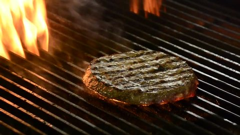 Frying burger meat on grill and fire.