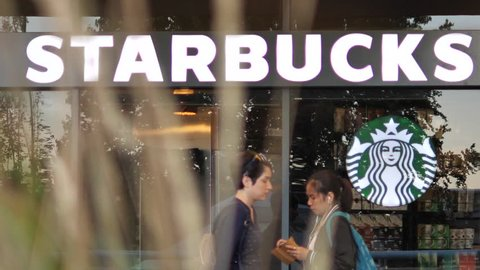 Burnaby, BC, Canada - September 14, 2017 : Slow motion of people walking through starbucks store with blurry leaves blowing in front of camera