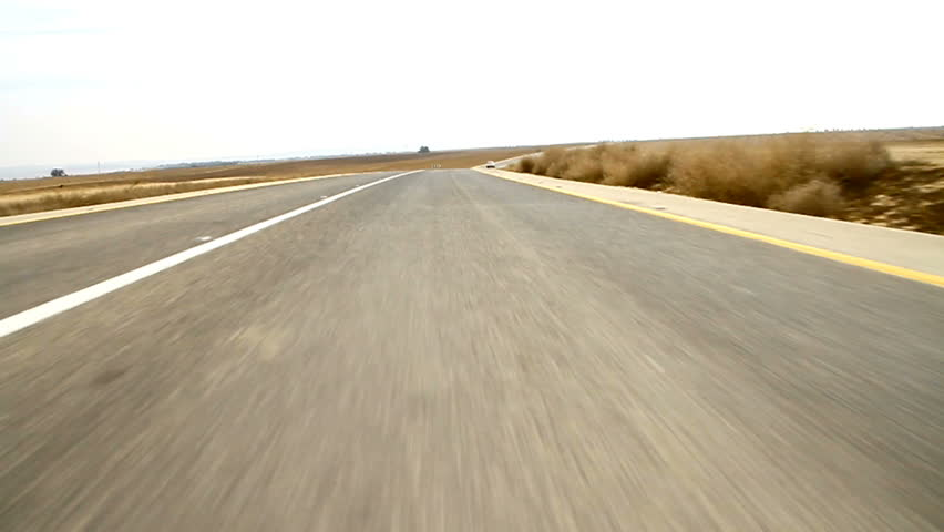 Road Comes Up To A Camera in Desert. Low angle view of driving car.