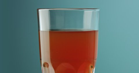 Close up of adding milk into tea in a tall glass on light blue background