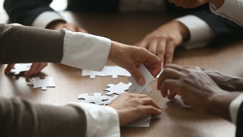 Close up view of business people hands trying to connect assembling jigsaw puzzle and join pieces on conference table in office, team help and support, finding right solutions in teamwork concept | Shutterstock HD Video #30832681