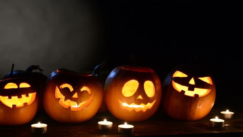 Halloween pumpkins in a row with candles overblack background with copy space for text above and light circle at background, front view, sliding video | Shutterstock HD Video #30860887