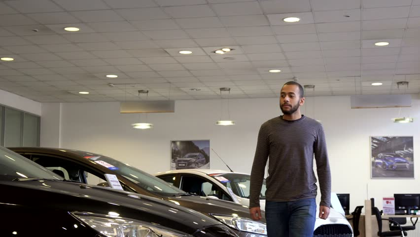 Handsome african american man walking along the car showroom. Attractive bearded guy stopping near the black sedan. Close up of young brunette male customer at the dealership | Shutterstock HD Video #30874561