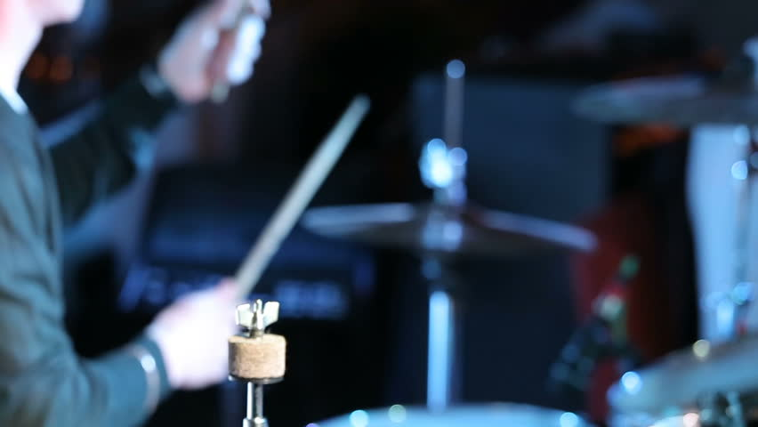 Rock n roll drummer plays music on concert. Close up. / Rock n roll drummer plays music on concert