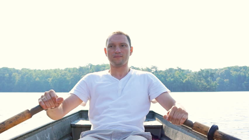 Serious focused concentrated young fit man rowing boat on lake in Virginia during summer in white shirt #30897211