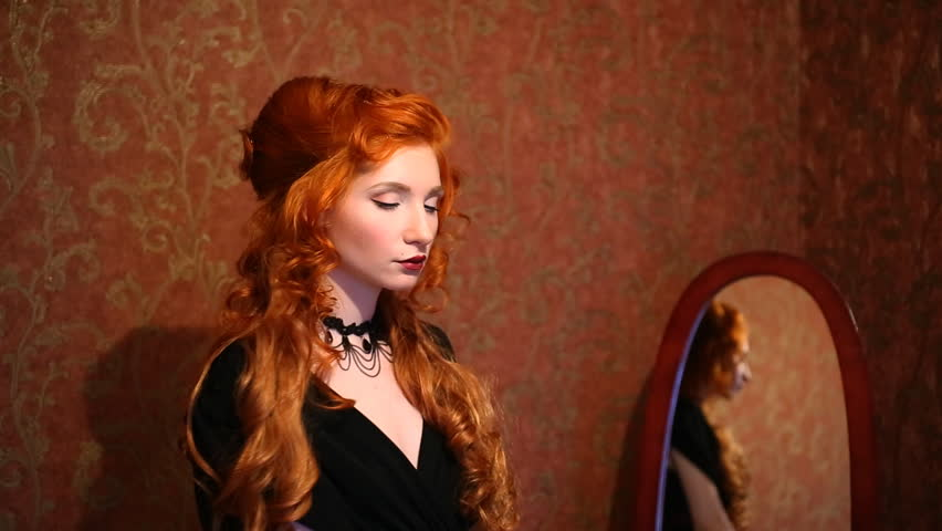 Portrait of a woman with long red curly hair in a black and red dress and
