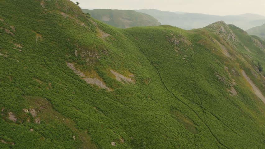 Aerial fly over of hikers reaching the top of a bracken covered fell side, eastern fells, Lake District.