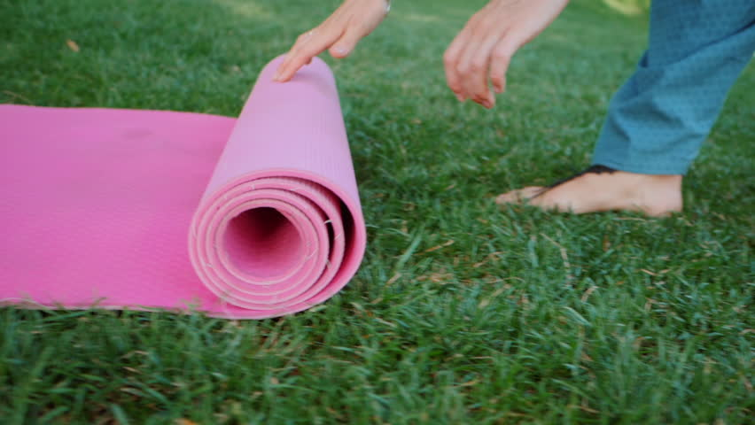Young woman doing yoga exercise - opening her pink yoga mat on green grass at the park. Slow motion.