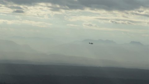 View from airplane of float plane silhouette flying in front of mountain range
