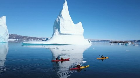 Aerial - Group Sea Kayaking at the base giant iceberg in Arctic East Greenland