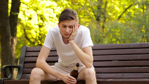 A drunk hipster sitting on a bench and drinking beer. Nausea and wobbling
