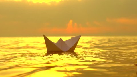 Kid with a paper boat in water over beautiful sunset. Little boy's hand puts paper ship on sea surface. Origami ship Sailing. Dreams, future, childhood, freedom or hope concept. Slow motion 4K