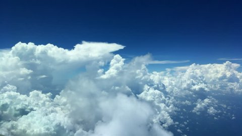 Aircraft flying past a thin patch of clouds. Large Cumulus clouds in the background. Blue skies above and the blue sea below.