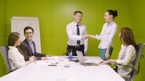 Chief speak positive speech to his business work team and shake hand to the best manager, complimenting and cheering, during business meeting in modern green office room
