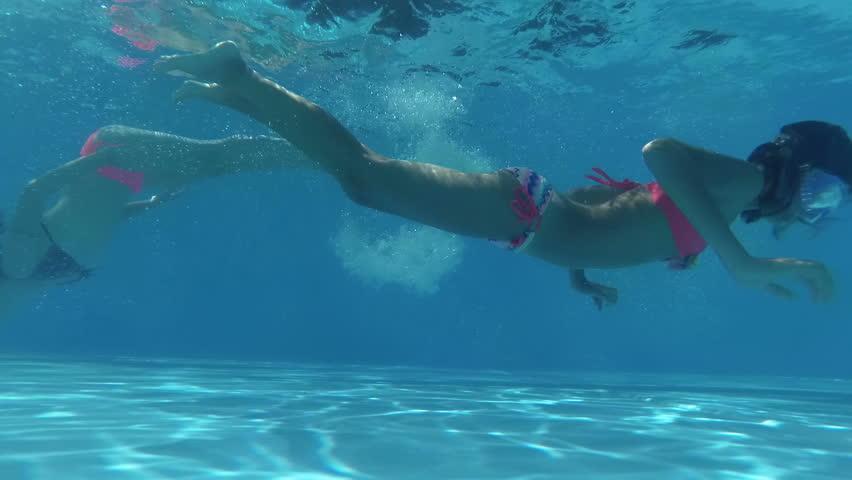 Happy smiling underwater girls swim to meet each other in swimming pool, beautiful healthy girls swim and having fun