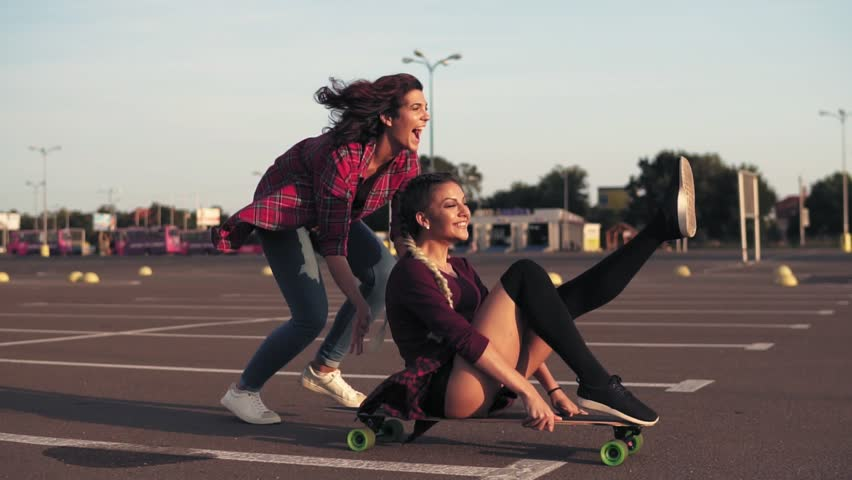Smiling woman sitting on a longboard while her friend is pushing her behind and running during sunset. Enjoying life. Lens flare. Slowmotion shot | Shutterstock HD Video #30999691