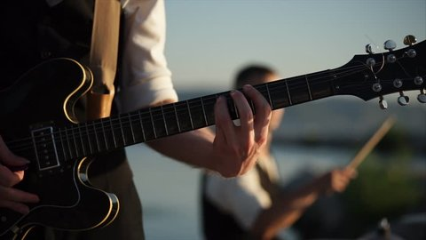 close up shot of a musical instrument, which is called a rhythm guitar, a young musician performs energetic music in the daytime in the open air