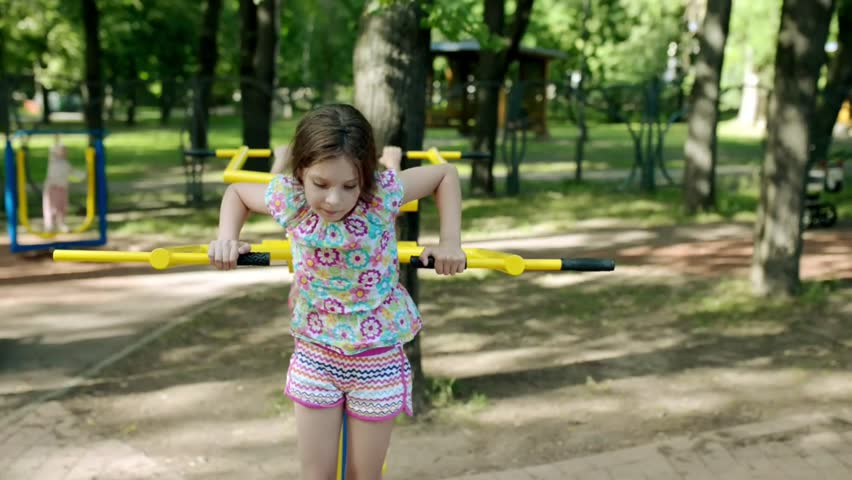 Little beautiful girl engaged on sports training apparatus in summer city park. | Shutterstock HD Video #31006912