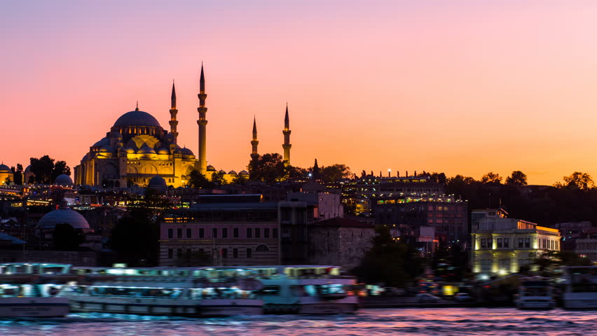 Timelapse view of Istanbul cityscape with Suleymaniye mosque with tourist ships floating at Bosphorus at night