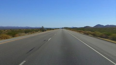The point of view of someone driving a car on Interstate 40 through the Mojave Desert near Barstow, CA.