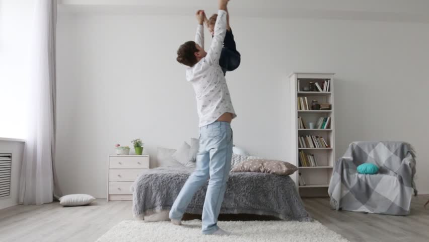 Little happy boy and his young father play together in bedroom  #31027108