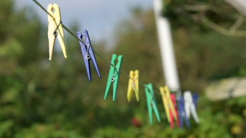 Some colorful clothespins are hanging on a washing line in front of green trees.