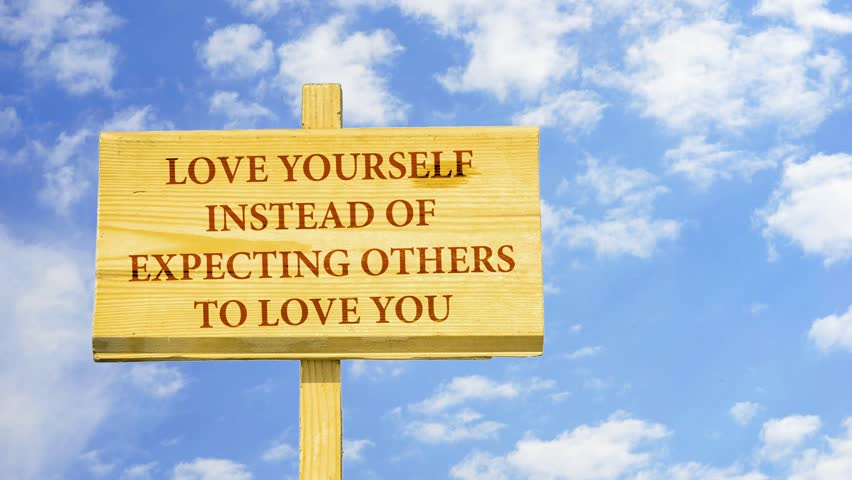 Love yourself instead of expecting others to love you. Words on a wooden sign against time lapse clouds in the blue sky.