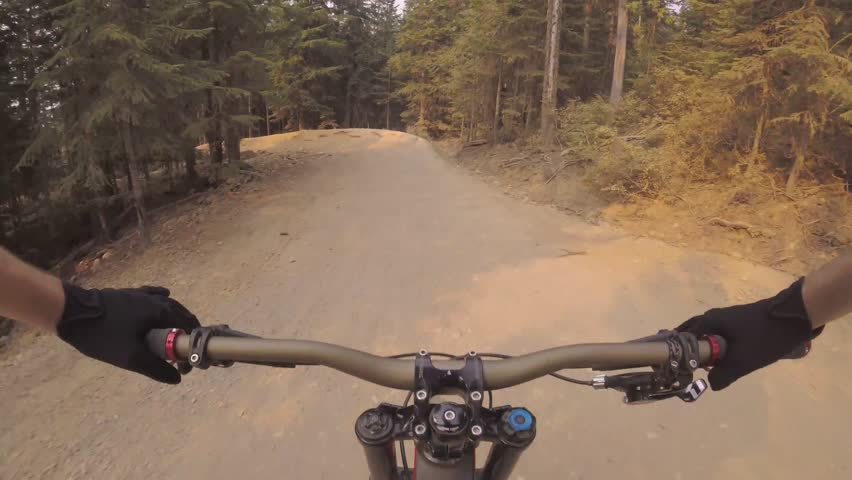 Beautiful 4k first person pov of man riding fast extreme sport mountain bike performing dangerous stunt on forest road | Shutterstock HD Video #31037866