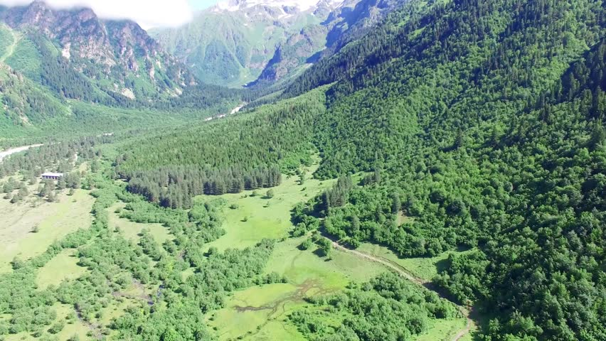 Flying over green fields and forest in Mountain Valley Aerial 4k video. Hiking Travel Tourism Caucasus Svaneti, Georgia.