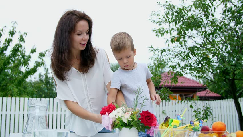 Summer, in the garden. Mom with a four-year-old son make a bouquet of flowers. The boy likes it very much, he is happy, having fun, The family spends their leisure time together. | Shutterstock HD Video #31053691