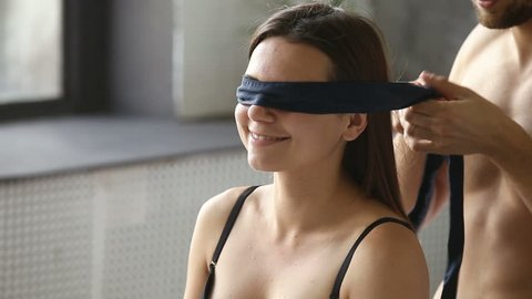 Young man blindfolding smiling woman sitting on bed, couple enjoy foreplay playing erotic role game with bdsm fetish black ribbon on eyes, husband embracing kissing wife before making love having sex
