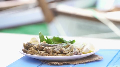 Turkish Hamsi Tava with lemon and arugula on blue table. Fried Anchovies by the sea at Foca Izmir. Copy space with sea and small boats background.