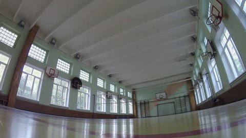 Light turning on in empty school gym with volleyball net.