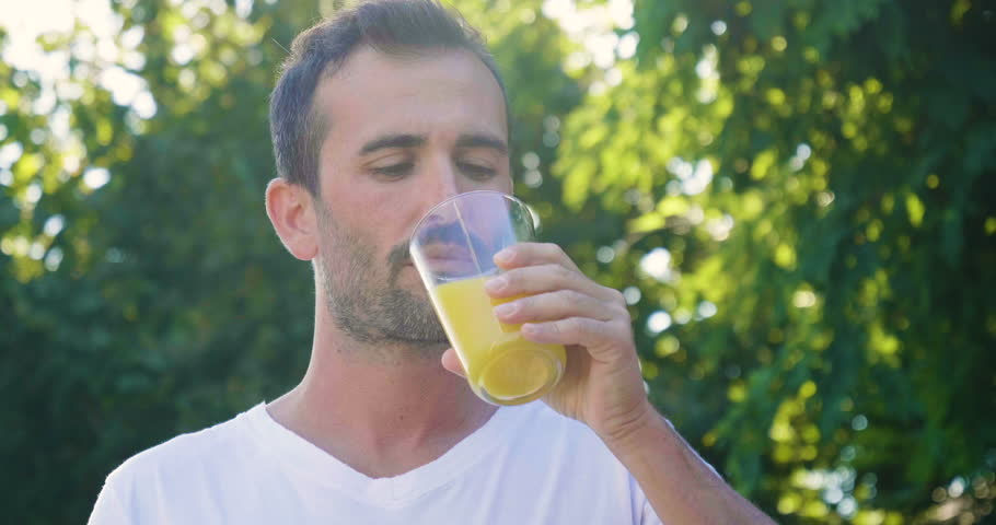 A man outdoors, immersed in nature, drinks a glass of orange juice rich in vitamins and dietetic. A genuine fruit juice that is good for the body. Concept of:healthy drinks,diet, vitamins,regular life