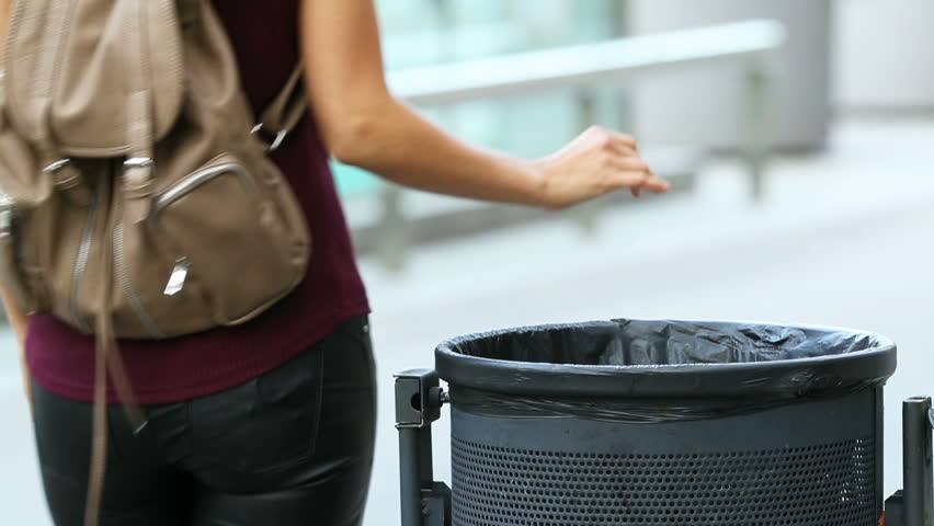 Woman walking on the street and throwing garbage to a trash bin