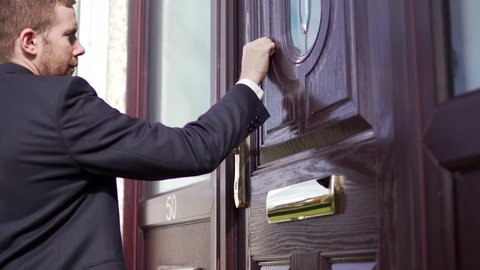 Man Knocks on Home Door in Suit, Waiting for the Homeowner at Front. White Caucasian Professional.