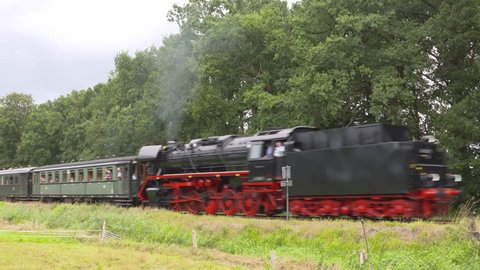 steam hauled passenger train - on camera + whistle - tender-first + passing by. Steam locomotive 44 1593-1 (1943, Lille) with vintage passenger wagons. VELUWE, THE NETHERLANDS