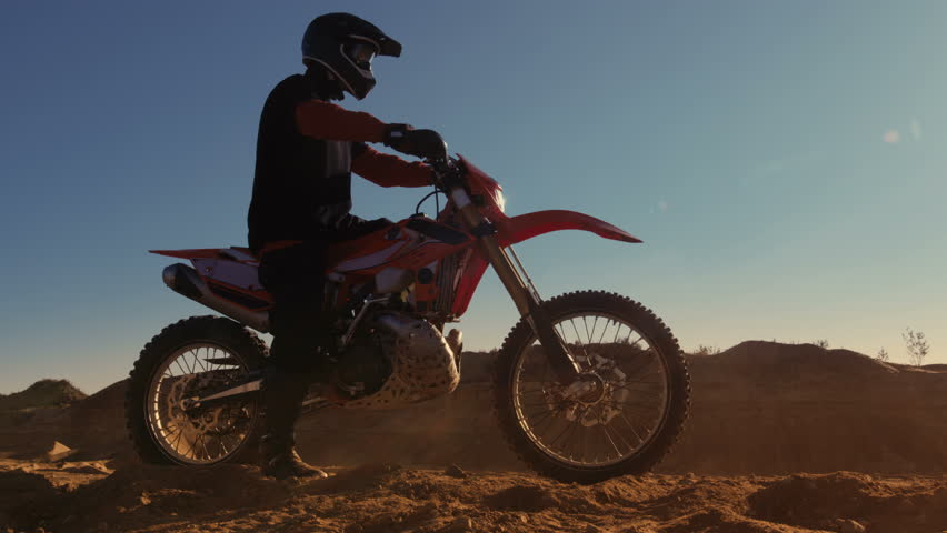 Side View Footage of the Professional Motocross Motorcycle Rider Driving on the Dune and Further Down the Off-Road Track. It's Sunset and Track is Covered with Smoke/ Dust/ Dirt. 4K UHD.