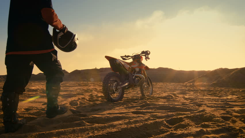 Low Angle Shot of the Professional Motocross Driver Putting on His Helmet and Getting Ready to Ride His FMX Dirt Bike on the Quarry Sand Terrain. Shot on RED EPIC-W 8K Helium Cinema Camera.
