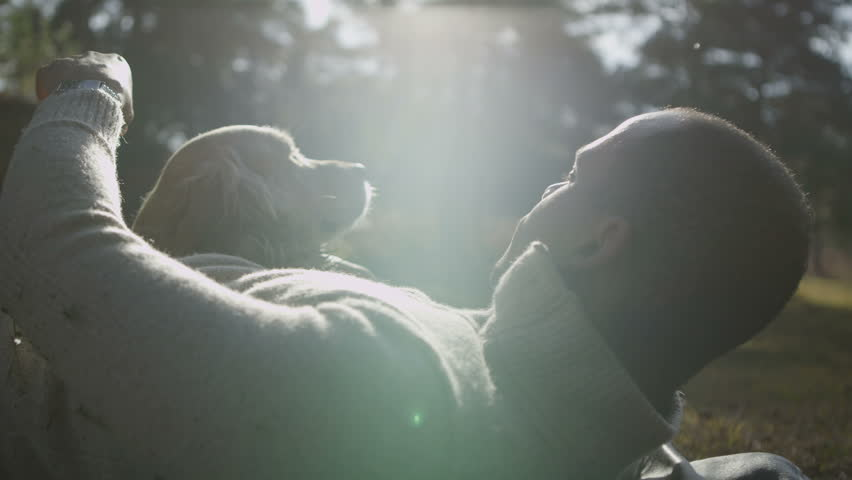 A man and his lovable pet dog laying down together in the early morning sunshine