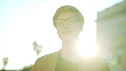 cheerful likeable boy in braces with glasses smiling and looking at camera on warm sunny day slow motion closeup