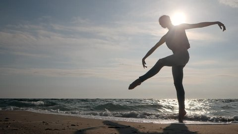 Young woman in casual style - jeans and black top dancing ballet at the beach. Attractive ballerina practices in stretching on sandy coastline in autumn. Slow motion. Beautiful scene. Gimbal shot