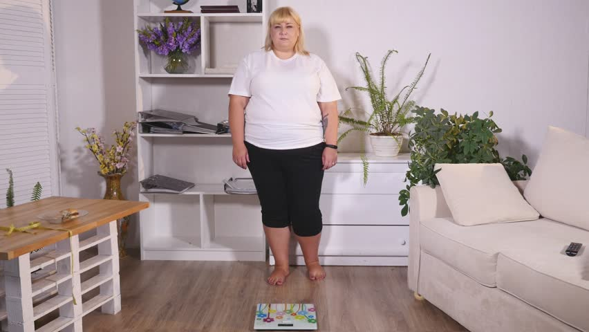 fat woman stands on the scales and shows class